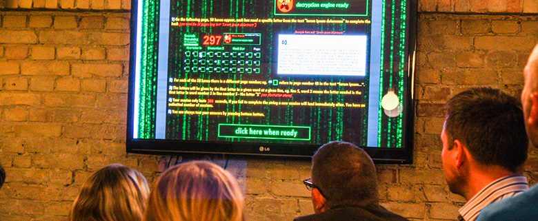 People looking at flat-screen monitor showing hacking codes etc.