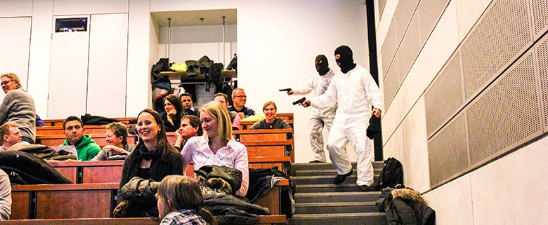 Terrorists in masks and white jumpsuits breaking into auditorium and threatening the audience with pistols