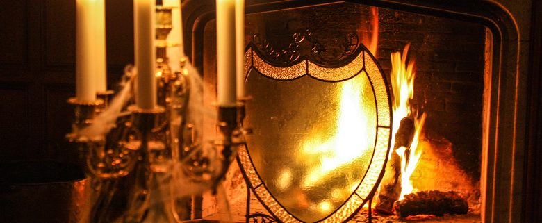 Candlelights in front of fireplace adorned with a large shield-crest