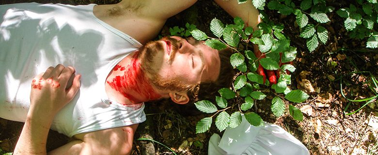 Murdered person in white tank-top lying in a bush with blood on neck